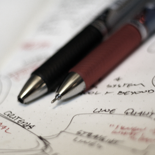 Close up photograph of a red pen and a black pen.