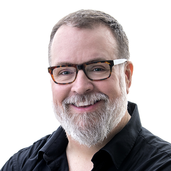 A portrait of Scott Reeves. He has short dark hair, a white beard and dark, square-rimmed glasses. He is facing the the camera and smiling.